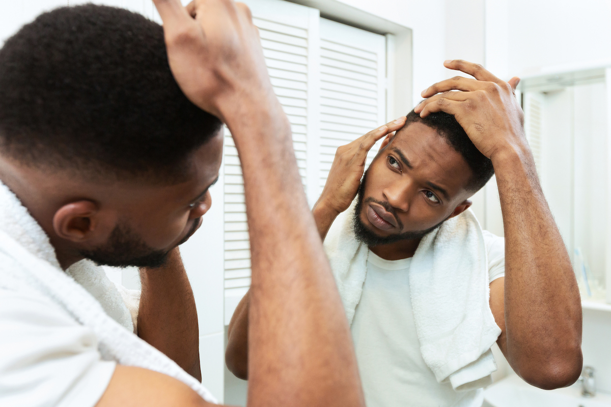 Hairloss concept. Young african man checking for thinning hair in mirror at bathroom